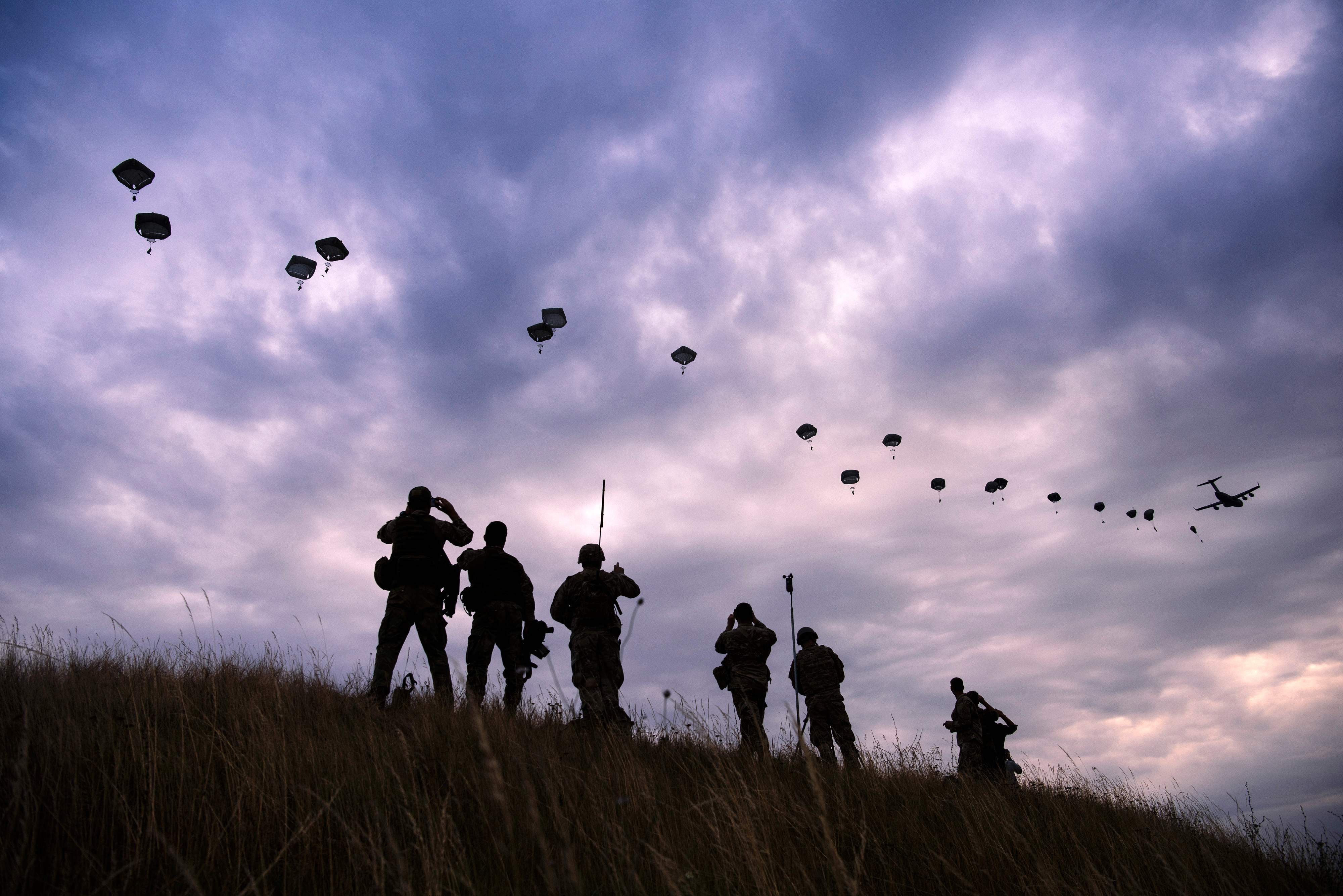 Soldiers siluetted against sky with parachuters