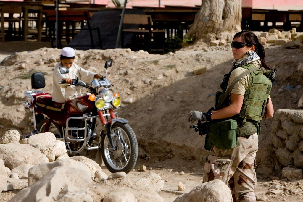 Female soldier in sunglasses in front of an afghan boy on a red motorcycle.