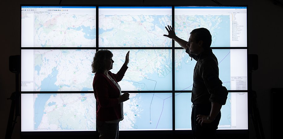 Two persons standig in front of a map