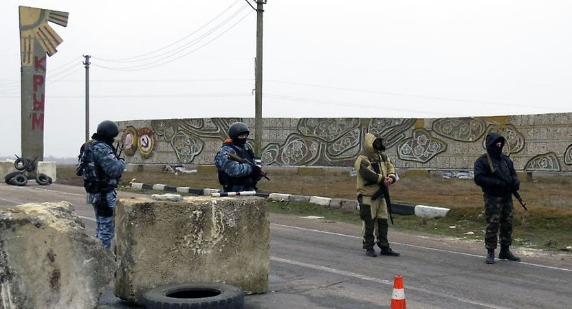 Unidentified military stand watch over a checkpoint to the Crimea region.